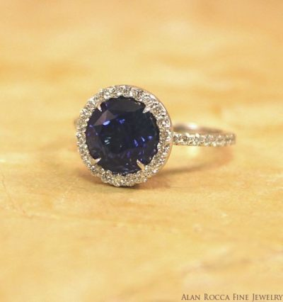 Round Blue Sapphire Surrounded by a Halo of Prong Set Round Cut Diamonds