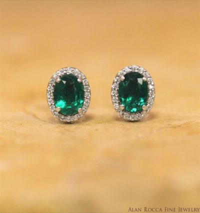 Oval Shaped Emerald Post Earrings Surrounded by a Halo of Prong Set Round Diamonds